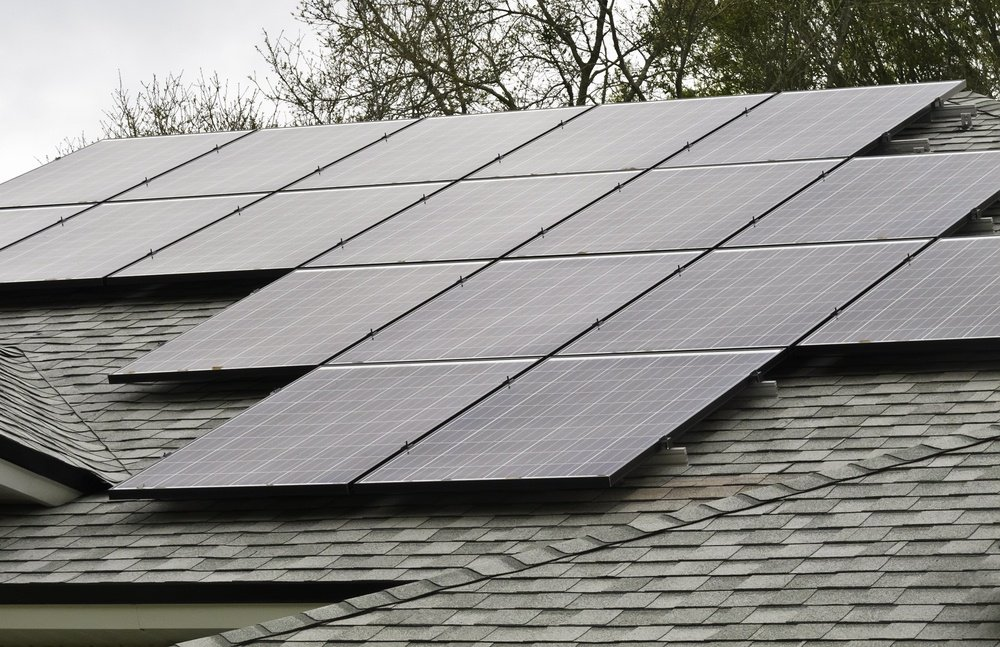 Array of solar panels on sloped roof of detached house on an overcast morning